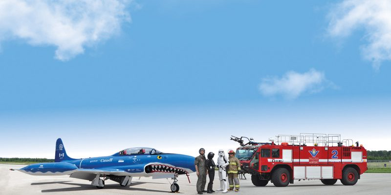 A pilot, fire fighter, and some star wars characters standing on the tarmac in front of a fire truck and and airplane at the Region of Waterloo International Airport's Aviation Fun Day