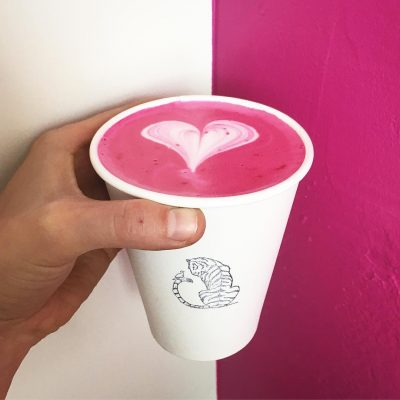 Pink latte in white Smile Tiger coffee cup.