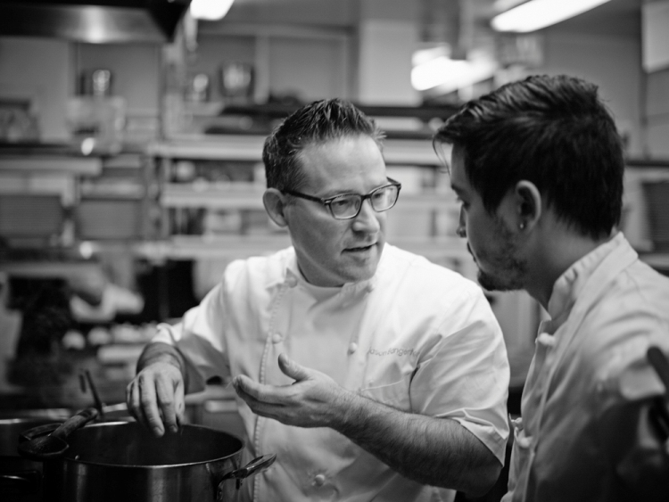 Black and white photo of Bangerter in kitchen talking to other chef.