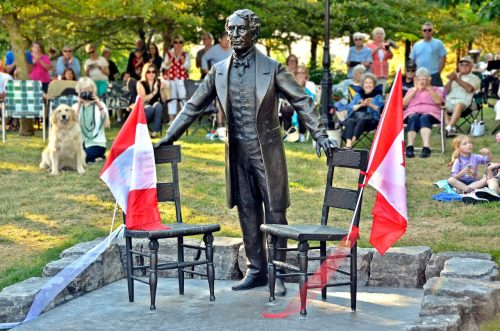statue of Sir John A. MacDonald standing with 2 chairs