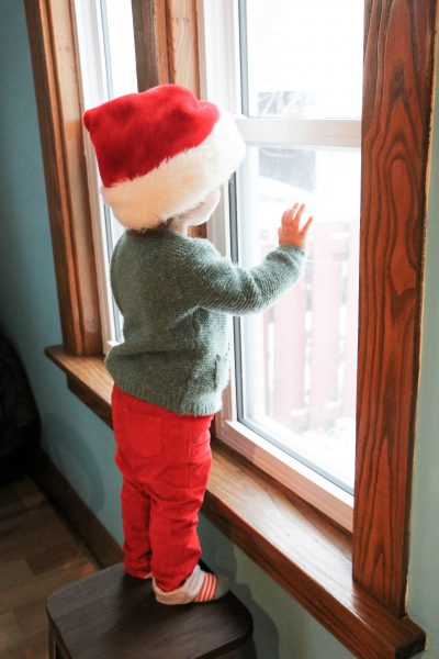toddler wearing a Santa hat looking out of a window