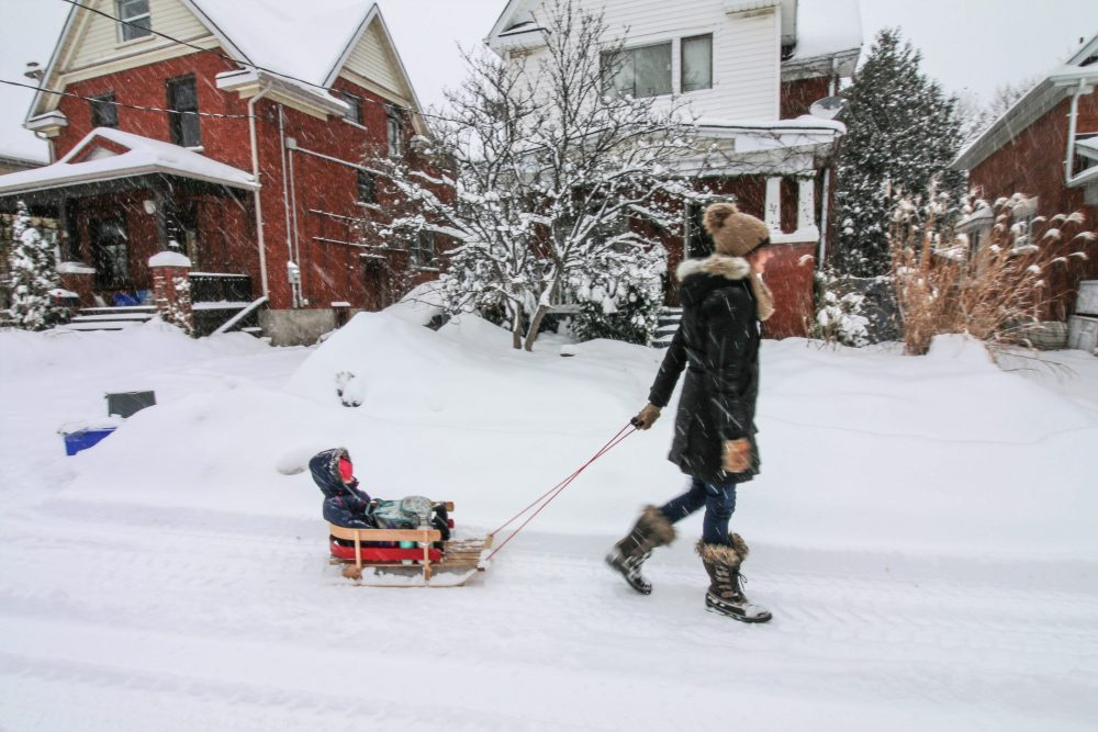 mother pulling a small child in a sled in the winter