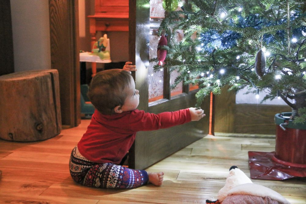 baby sitting on the floor and touching a Christmas tree