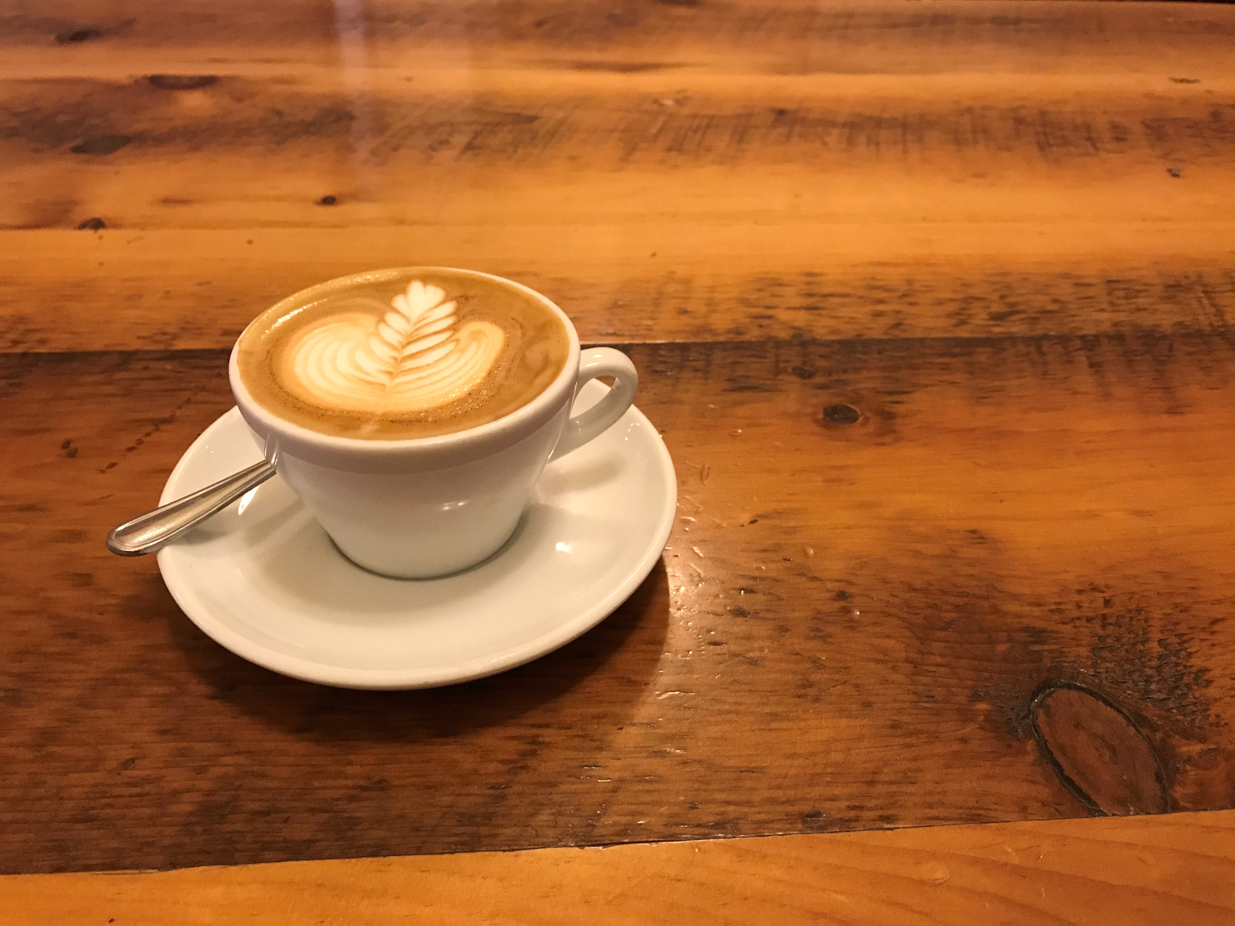 latte in a white cup on a wooden table