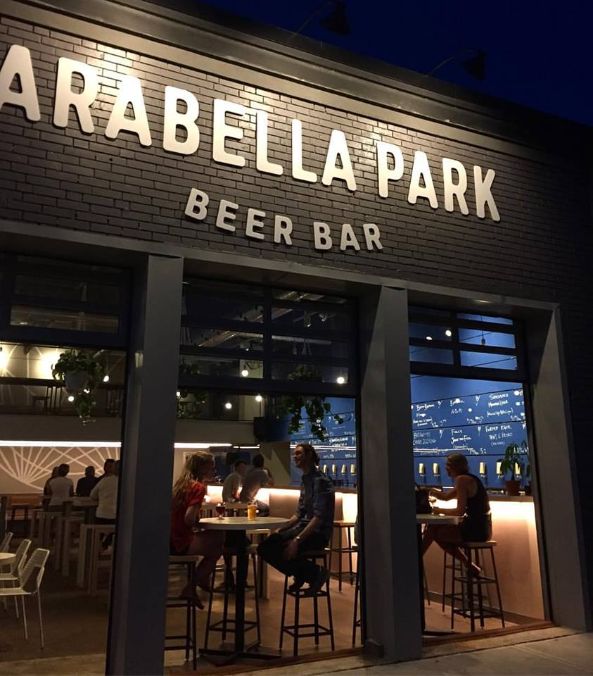 Arabella park beer bar with patio doors open on a summer evening with people inside enjoying local craft beer on tap at Belmont Village in Kitchener, Ontario