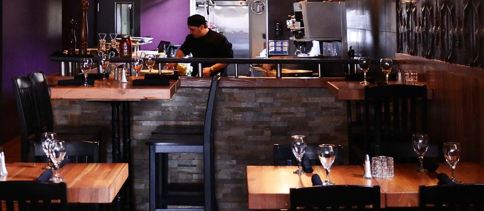view of the dining room/ kitchen area with Chef preparing dinner menu at King Street Trio in UpTown Waterloo, Ontario