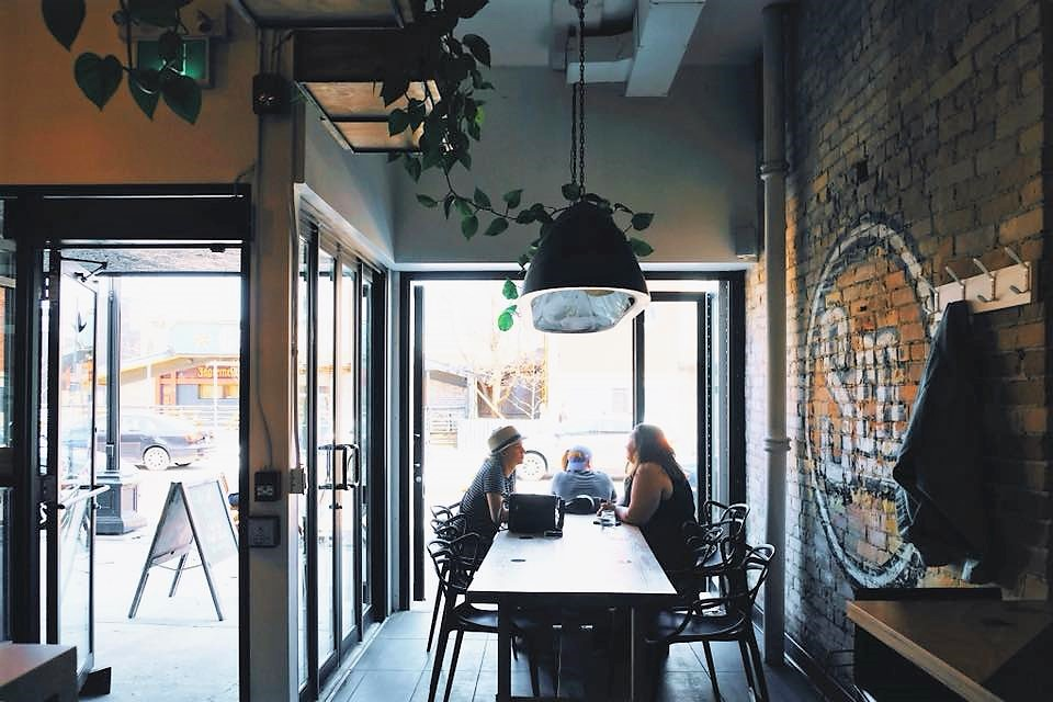 Two people sit inside the trendy cafe, Settlement Co., located in UpTown Waterloo, Ontario