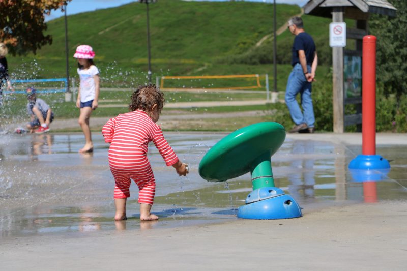 child playing in a splashpad in Waterloo Region