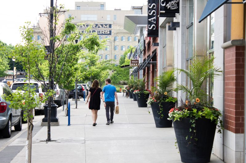 couple walking hand in hand in Uptown Waterloo (summertime)