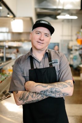 Chef Brian McCourt of Ignite Group standing in the kitchen of Graffiti Market