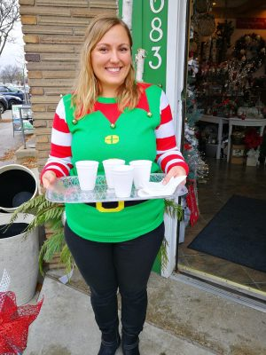 and elf serving hot chocolate at Christmas in the Village