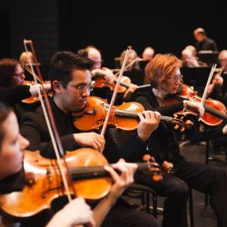 Members of the KW Symphony playing the violin on stage