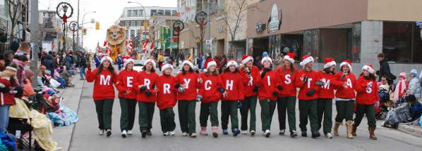 Volunteers spelling out Merry Christmas in the Kitchener Santa Claus Parade