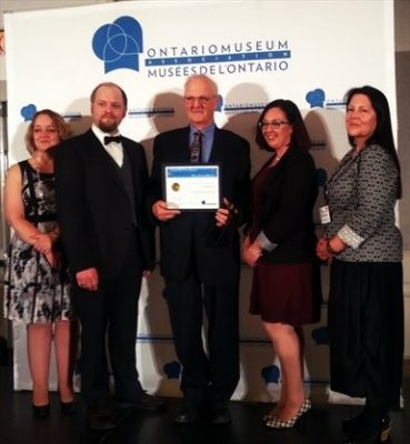 Warren Stauch (centre), volunteer with the Waterloo Region Museum accepting the Volunteer Service Award of Excellence with the OMA committee.