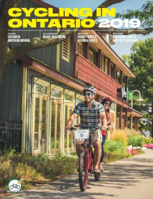 Ontario By Bike Magazine 2019 Cover - Man and women cycling in front of a home