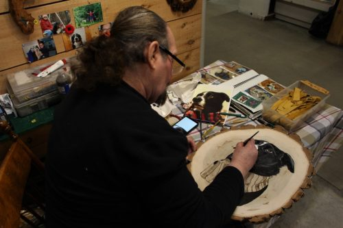 artist Angus Burns working on a commission piece of a dog at White Wolf & Friends at the St. Jacobs Farmers' Market