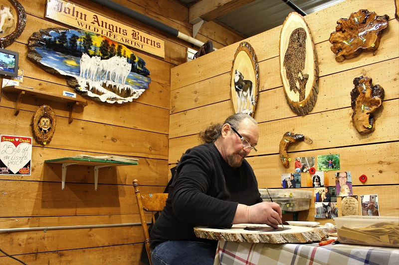 artist Angus Burns, owner of White Wolf and Friends, working on a piece of art created on wood in his booth at the St. Jacobs Farmers' Market