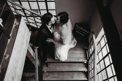 black and white photo of a bride and groom sharing a kiss in a stairwell - photo by photography from the soul