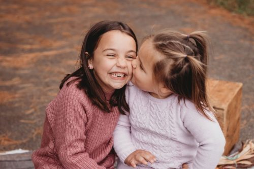 one little girl giving another little girl a kiss on the cheek - photo by photography from the soul