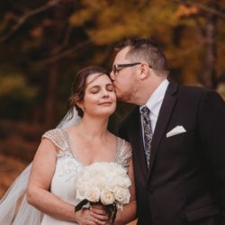 an outdoor fall photo of a bride and groom, the groom is kissing the bride's forehead - photo by Photography from the Soul