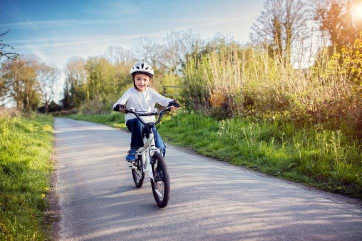 young boy cycling on a City of Kitchener trail in the springtime