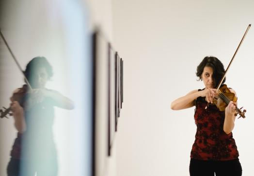 one of the installations showing a female violinist performing in front of one of the installations of Soundings at the Kitchener Waterloo Art Gallery