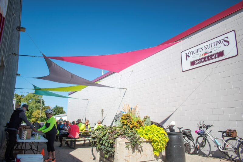 cyclists stopping for a bite to eat outdoors at picnic tables at Kitchen Kuttings in Elmira during the Ontario by Bike Waterloo Guelph Explorer