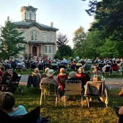 guests seated on the front lawn for an event at Castle Kilbride