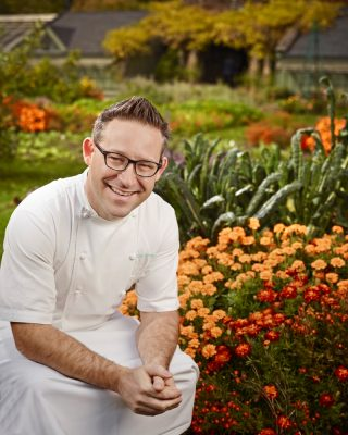 Jason Bangerter seated in front of flowers.