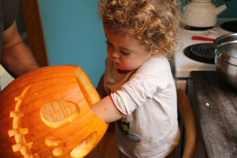 child carving a pumpkin for Halloween