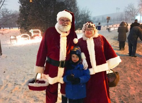 A boy standing with Santa and Mrs. Claus