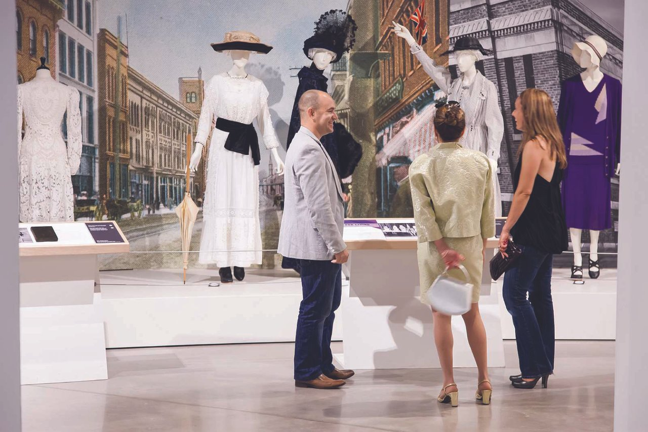 two women and a man looking at one of the displays of historic outfits on display at the Fashion History Museum in Cambridge
