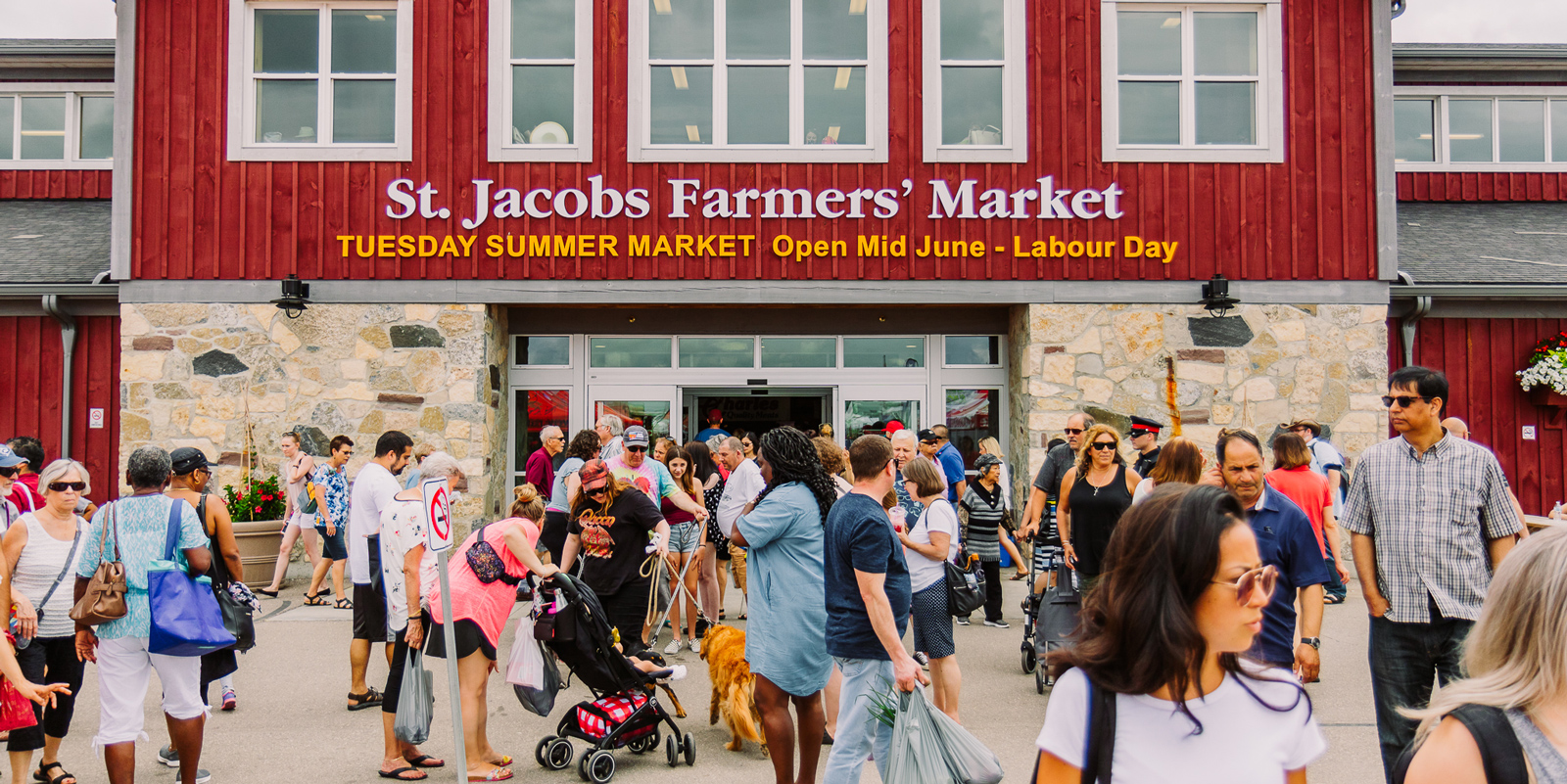 Visitors walking in front of the St. Jacobs Farmers' Market main building in St. Jacobs