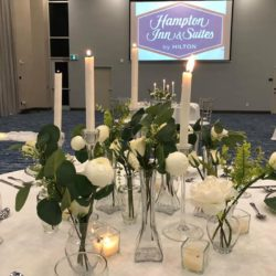 a round table beautifully decorated with flowers and candles for a wedding in a venue room at Hampton Inn and Suites St. Jacobs