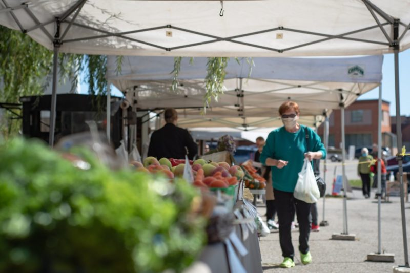 distant view of the outdoof farmers' market in Elmira showing vendors and their local produce as well as shopping with bags of food that they have purchased