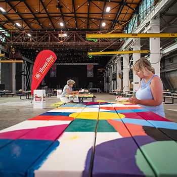 artist Angela Grasse seated at a wooden picnic table inside a large industrial building, painting a colourful quilt design onto the table
