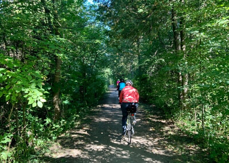 Cycling participants in Ontario by Bike's Waterloo Guelph Explorer cycling through a treed trail in Waterloo Region