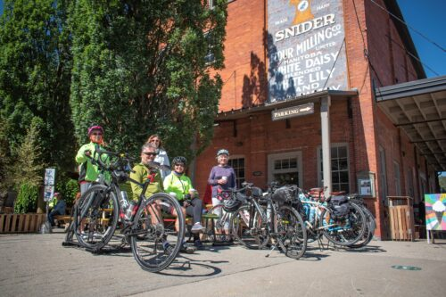 cyclists participating in the Ontario by Bike Waterloo Guelph Explorer taking a break and enjoying the Village of St. Jacobs