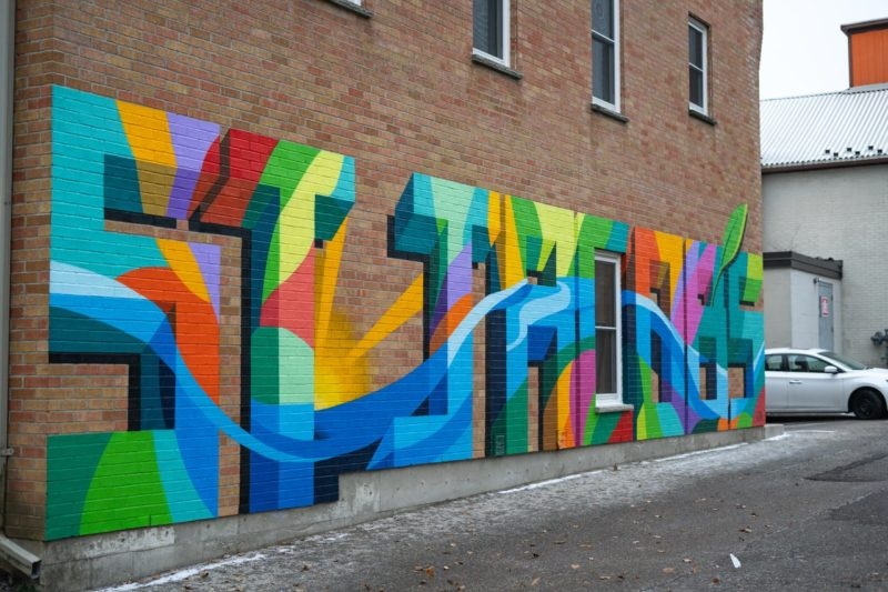 a colourful mosaic wall mural on the outside of a building in the village of St. Jacobs that spells out the words St. Jacobs