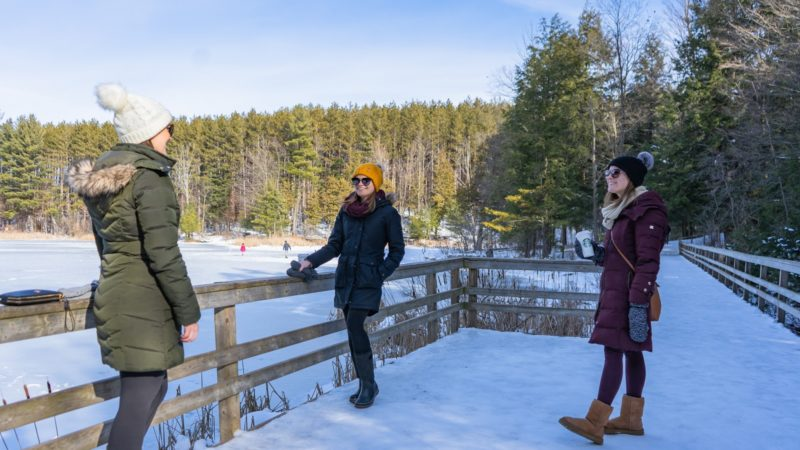 three girlfriends socially distanced, standing at a lookout point on a sunny, snowy day at Huron Natural Trail in Kitchener, one is holding a takeout coffee cup