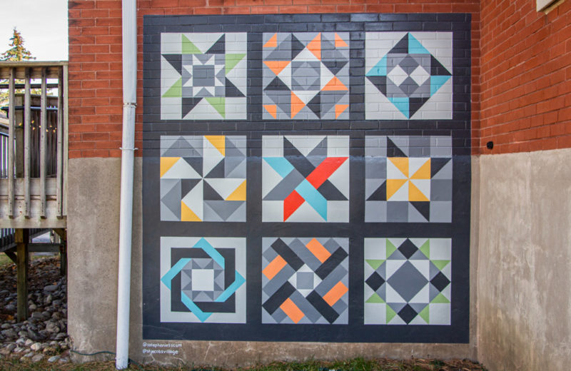 Artist Stephanie Scott's painted quilt mural on the side of a brick church in St. Jacobs