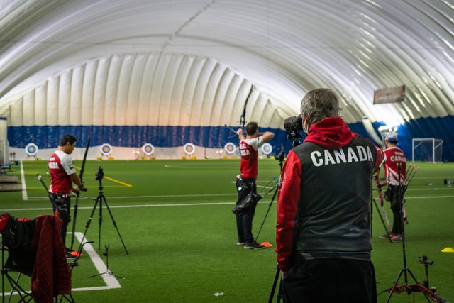 male athletes with Archery Canada's Recurve High Performance program aiming at targets as they practice during an Olympic training camp being held at the ComDev Indoor Soccer Centre in Cambridge