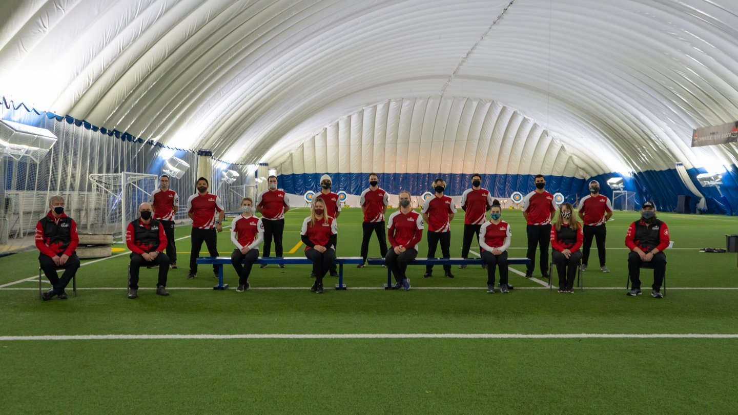 Archery Canada's Recurve program team posing for a team picture, while wearing masks and socially distancing, at the ComDev Indoor Soccer Centre in Cambridge