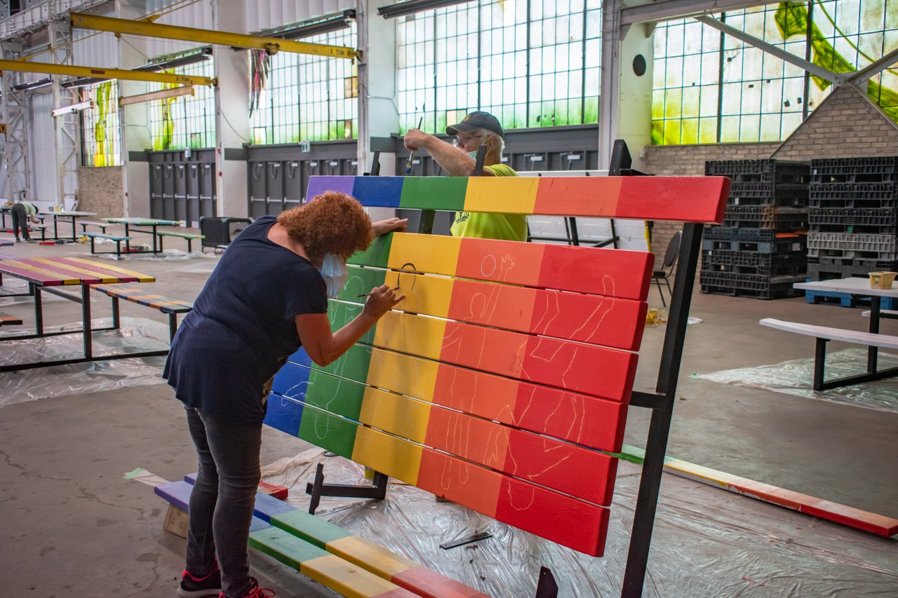Artist Wilma Vanderleeuw working on her multi-coloured Art Fresco picnic table inside Lot 42 in Kitchener: the table would find a home at Cafe Pyrus