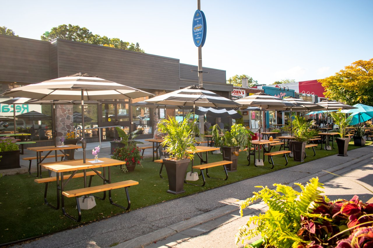 picnic tables and table umbrellas lined up along the public patio area which includes astro turf and decorative planters in Belmont Village in Kitchener