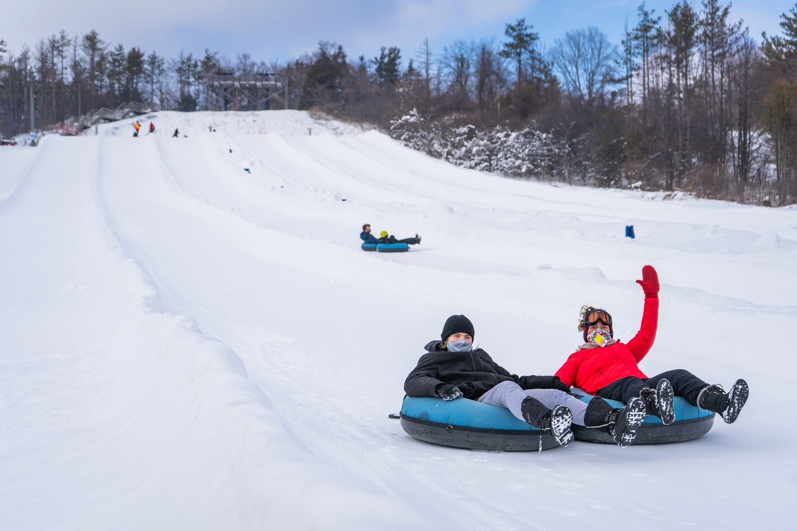 a woman and a teenager in snow tubes, having fun going down the hill at Chicopee Tube in Kitchener