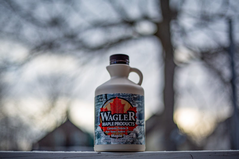 a container of Wagler Maple Products maple syrup placed in the forground, with the farm in the distant background