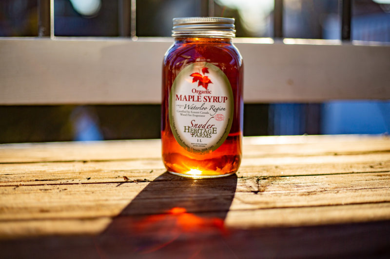 a branded mason jar of maple syrup sitting on a bench outdoors at Sbyder's Heritage Farms in Bloomingdale