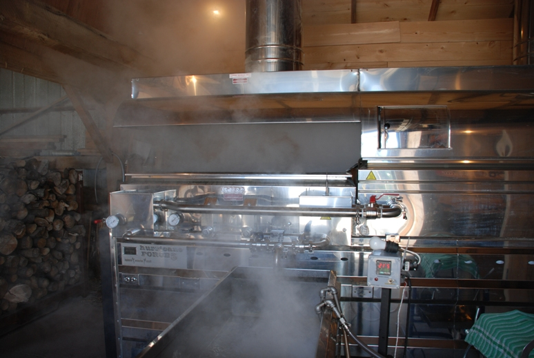 maple sap boiling with steam rising from the steel vats at the sugar bush at Snyder Heritage Farms in Bloomingdale