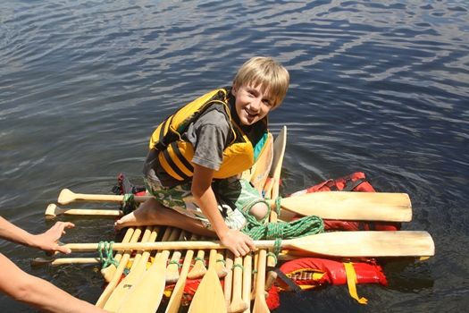 youth wearing a life jacket and crouching on lined up paddles that are laying on life jackets on the open water at the Survive and Thrive camp at Camp Ki-Wa-Y through the YMCA of the Three Rivers Waterloo Region